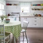 В качестве аксессуаров яркая цветная посуда и вазочка с цветами в интерьере загородной кухни