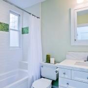 Фрагмент, выложенный зеленой мозаикой для создания зеленого интерьера ванной комнаты