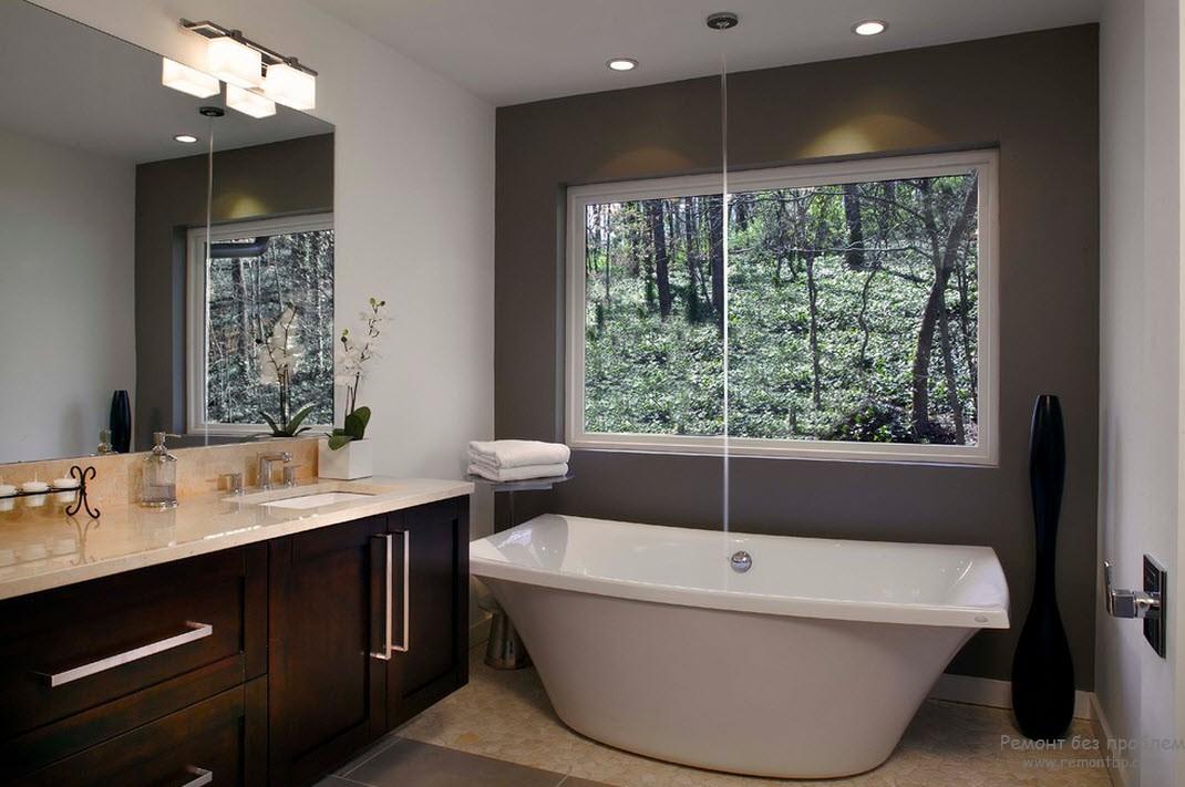 Черная напольная ваза оригинальной формы очень элегантно дополняет интерьер серой ванной комнаты