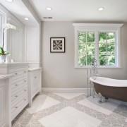 Зеленый цветок на подокннике и зеленые картины освежают интерьер серой ванной комнаты