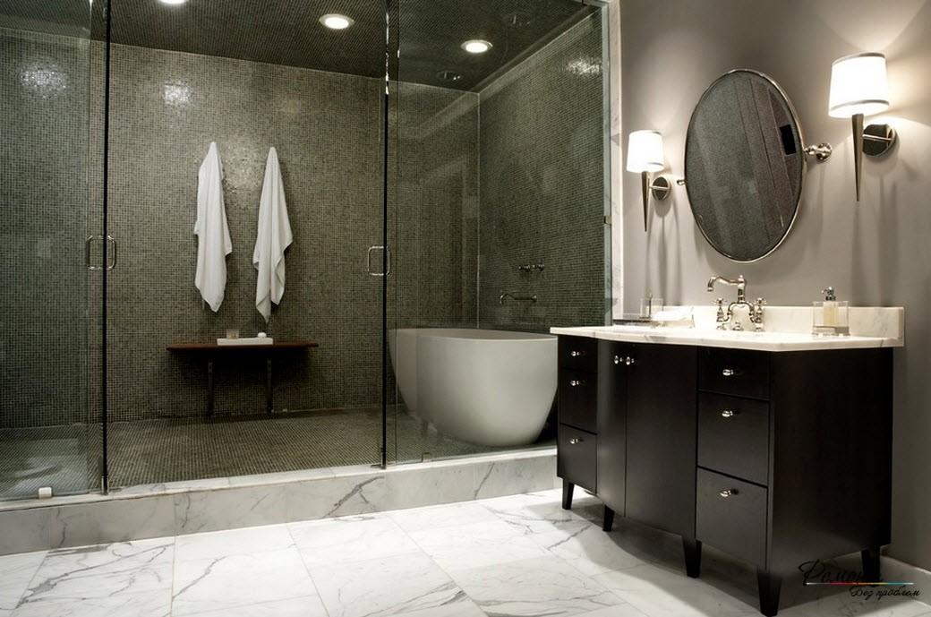 Мелкая блестящая плитка с глянцевой поверхностью создает видимость глубины помещения с ванной и душем