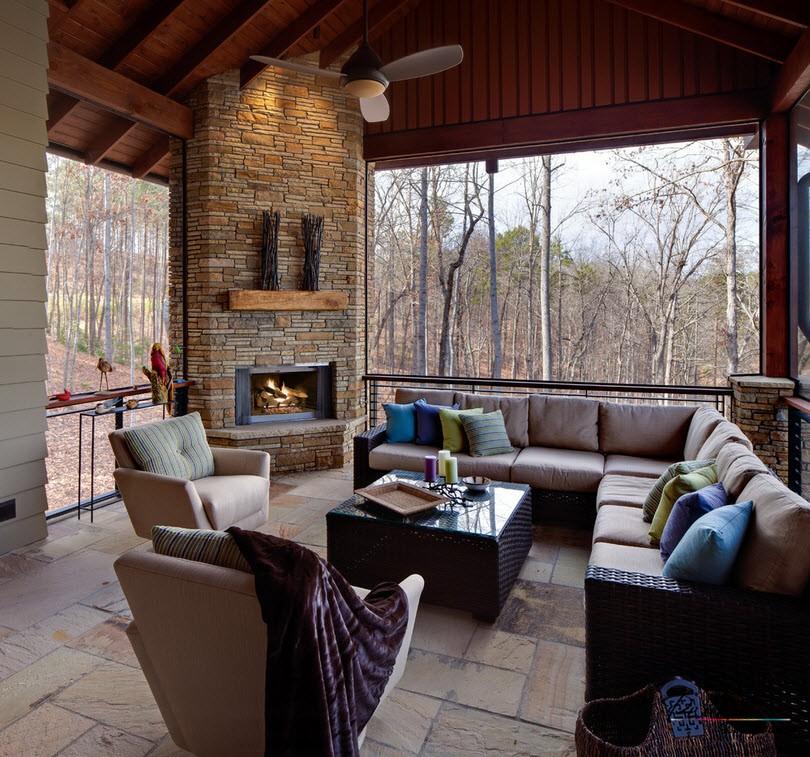 Интерьер гостиной загородного дома с угловым камином из кирпича