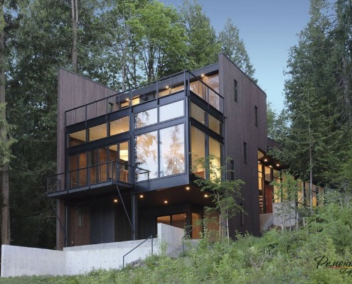 Дом с темным фасадом и панорамной стеной