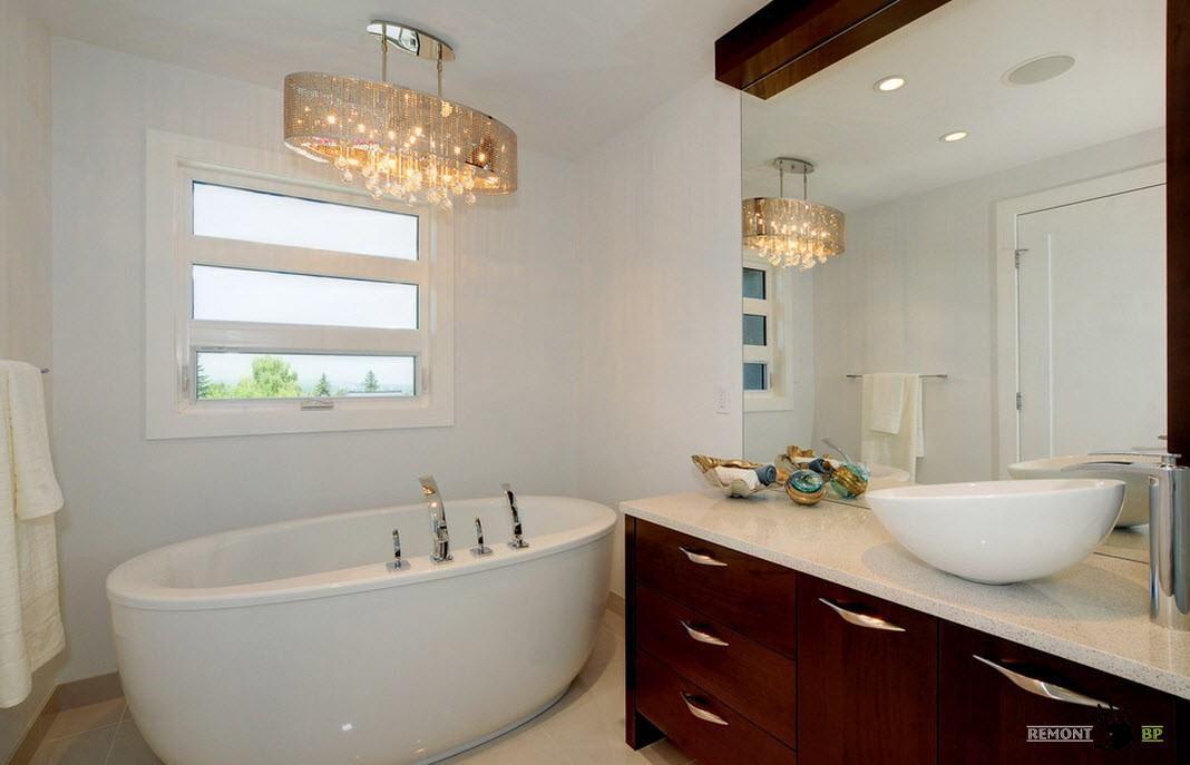 Люстра над овальной ванной