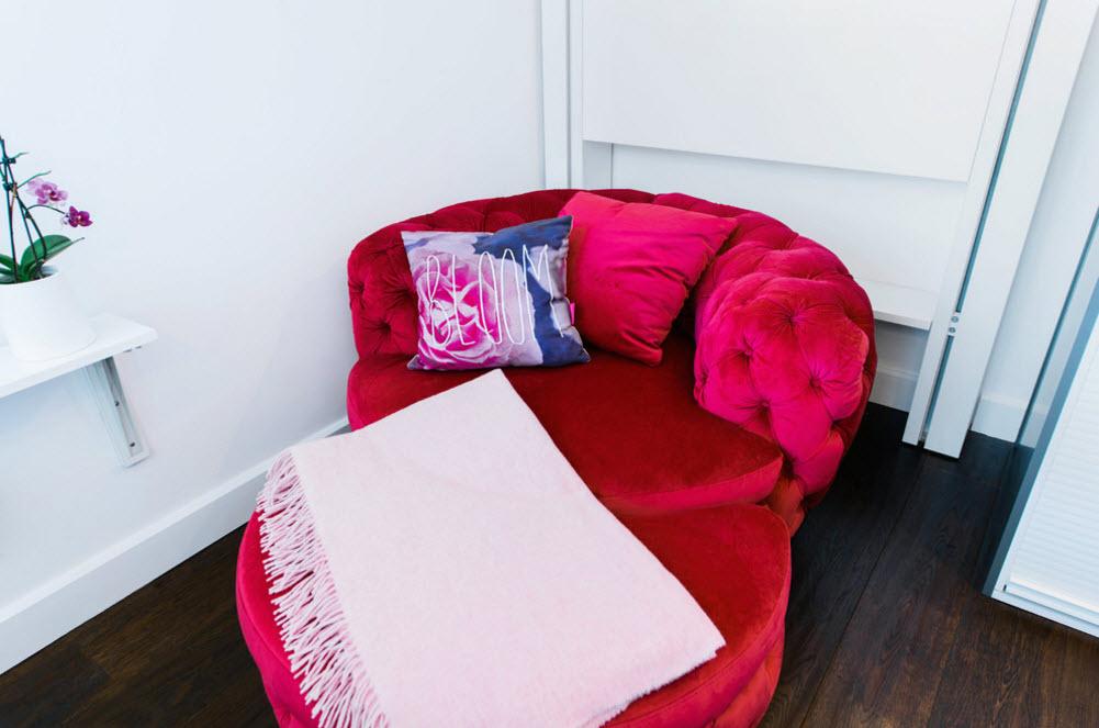 Яркий диванчик и пуф занимают место кровати