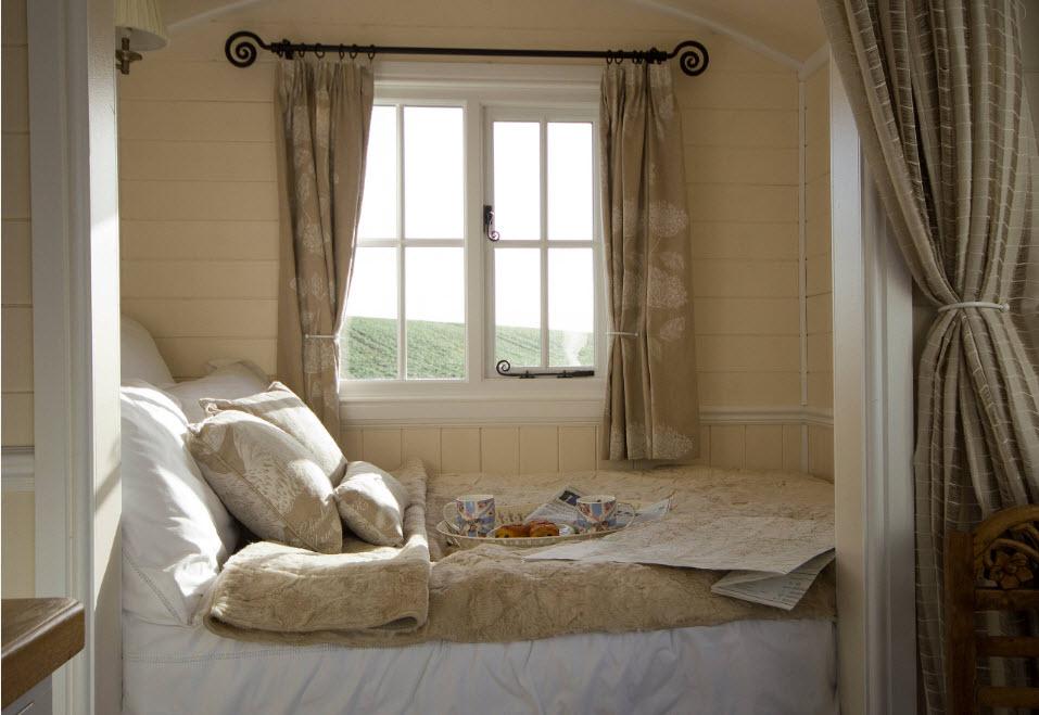 Небольшая кровать у окна за шторой
