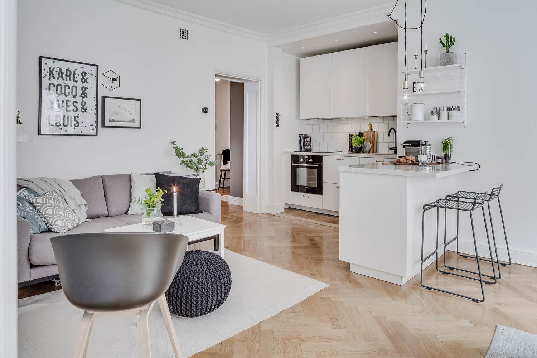 дизайн совмещенной кухни-гостиной с белой барной стойкой