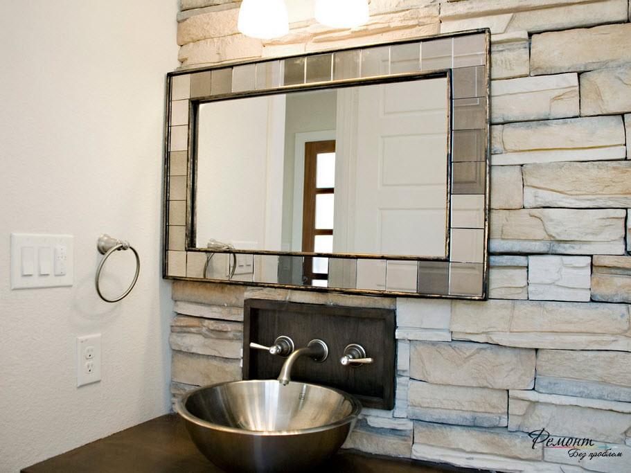Ванная комната, стена которой отдедлана грубым крупным камнем