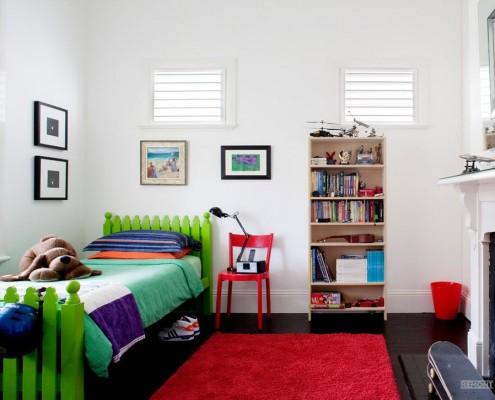 Зеленая кровать и красный коврик в детской