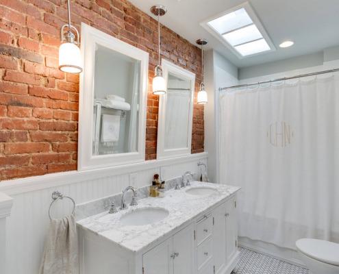 Два белых зеркала на кирпичной стене в ванной