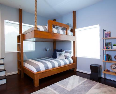 ДВухъярусная кровать с полосатым матрасом между окнами в углу