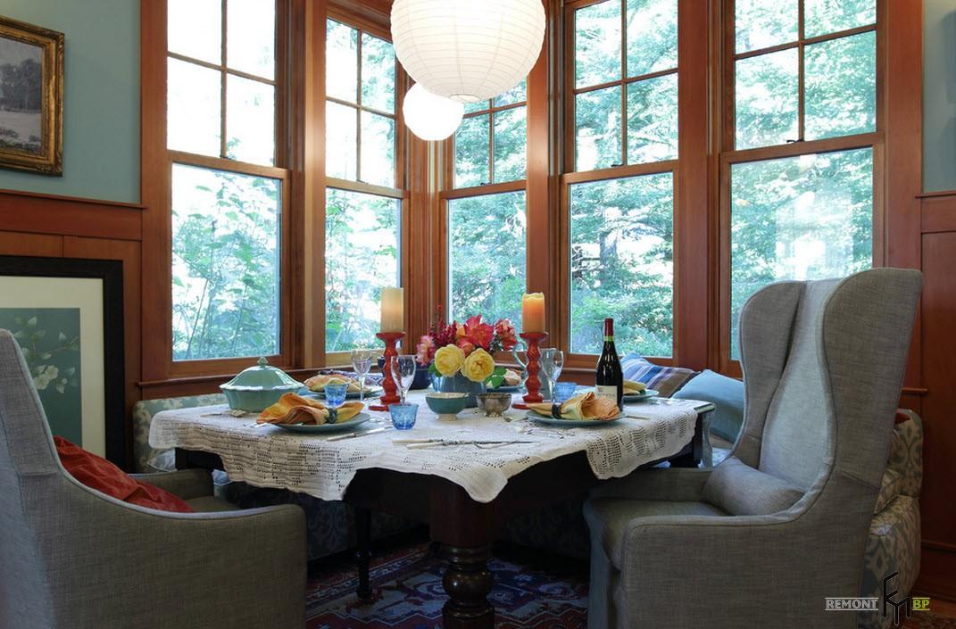 Круглый сервированный стол возле углового окна
