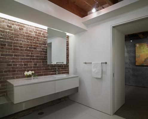 Белые цветы на в вазе на фоне кирпичной стены в ванной