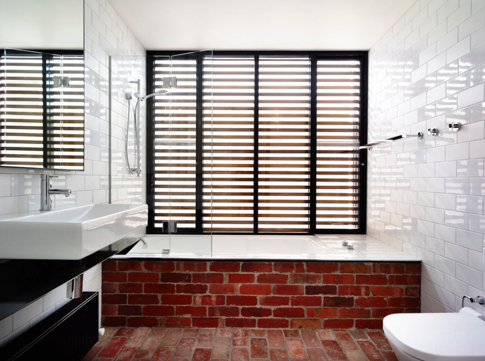 Кирпичная кладка на стене в ванной под окном