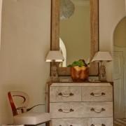 Зеркало в стариной раме над белым комодом
