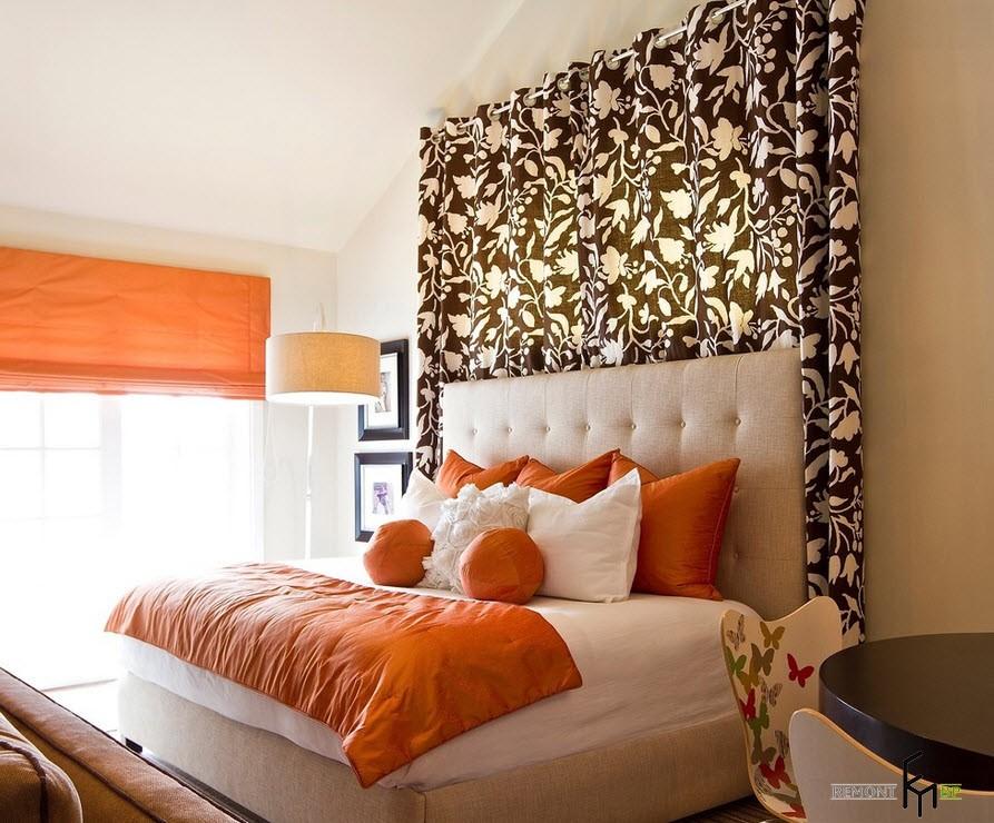 Оранжевые подушки на фоне бежевого изголовья