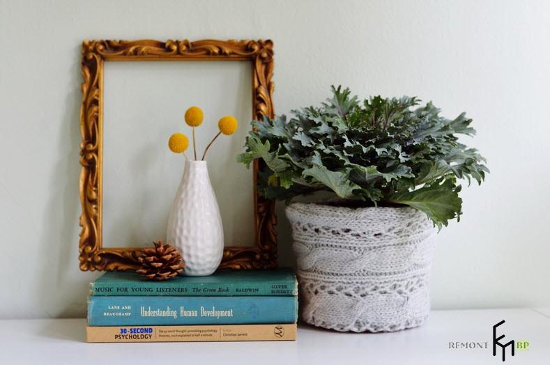 Вязаный горшок с цветком рядом с белой вазочкой