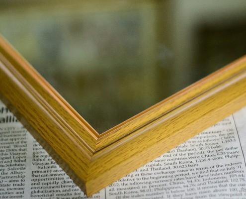 Угол деревянной рамы для зеркала на газете
