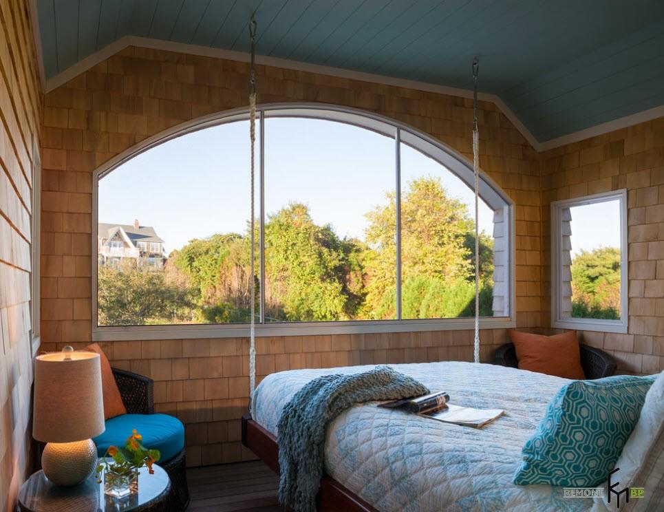 Подвесная кровать у арочного окна