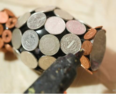 Пистолетом наклеивают последние монеты на вазу