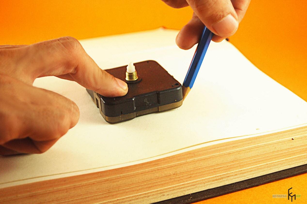 Карандашом обводят контуры на книге